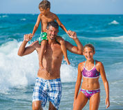 Father and children playing in the sea Stock Photography