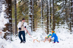 Father and children playing in snow Royalty Free Stock Images