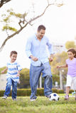 Father With Children Playing Soccer In Park Together Royalty Free Stock Photos