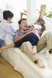 Father And Children Playing On Sofa At Home Stock Images