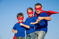 Father and children playing superhero at the day time. People having fun outdoors. Concept of friendly family Royalty Free Stock Images