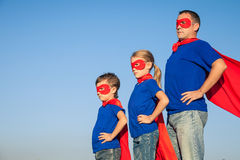 Father and children playing superhero at the day time. People having fun outdoors. Concept of friendly family Stock Photos