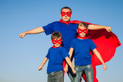 Father and children playing superhero at the day time. People having fun outdoors. Concept of friendly family Royalty Free Stock Photo