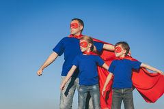 Father and children playing superhero at the day time. People having fun outdoors. Concept of friendly family Stock Photo