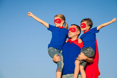 Father and children playing superhero at the day time. People having fun outdoors. Concept of friendly family Stock Images