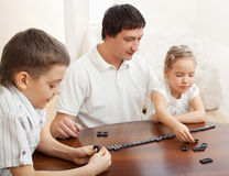 Father with children that plays dominoes Royalty Free Stock Image