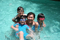 Father and children in the pool. Father and children playing happily in the pool Royalty Free Stock Image