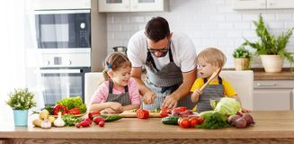 Father with children preparing vegetable salad Royalty Free Stock Photo