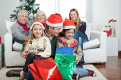 Father And Children With Presents During Christmas. Happy father and children with presents while family sitting on sofa during Christmas at home Stock Photos