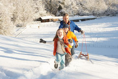 Father And Children Pulling Sledge Up Snowy Hill. Laughing Royalty Free Stock Images