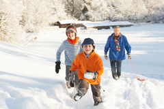 Father And Children Pulling Sledge Up Snowy Hill royalty free stock photography