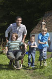 Father And Children Racing With Wheelbarrow Outside Cottage Stock Images