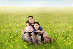 Father and children read book on meadow Stock Photography