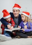 Father With Children Reading Book During Christmas. Full length portrait of father with children reading book at home during Christmas Royalty Free Stock Photography