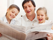 Father with children reading a newspaper Royalty Free Stock Image