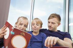 Father and children reading storybook at home Royalty Free Stock Photo