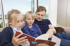 Father and children reading storybook on sofa at home Royalty Free Stock Images