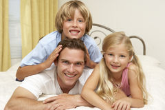 Father And Children Relaxing On Bed At Home Royalty Free Stock Photos