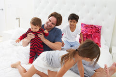 Father And Children Relaxing In Bed Together Stock Photography