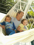Father and children (5-8) relaxing in hammock on balcony, smiling, man sleeping, portrait (tilt) Royalty Free Stock Image