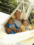 Father and children (5-8) relaxing in hammock on balcony, smiling, portrait (tilt) Stock Photography