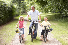 Father and children riding bikes in countryside Stock Image
