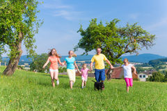 Father with children running on green meadow grass Royalty Free Stock Images