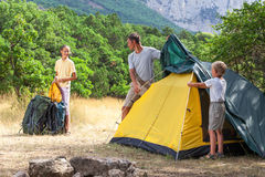 Father with children setting a tent Stock Photo