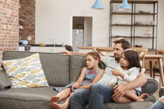 Father And Children Sit On Sofa In Lounge Watching TV Stock Photos