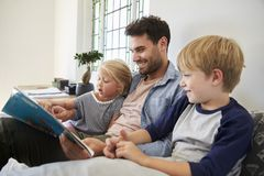 Father With Children Sitting On Bed Reading Book Together Royalty Free Stock Photo