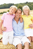 Father And Children Sitting On Straw Bales In Harv Royalty Free Stock Photos