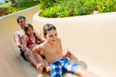Father and Children Sliding Down Water Slide Royalty Free Stock Images