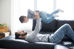 Father And Children On Sofa At Home Watching TV Together. A Father And Children On Sofa At Home Watching TV Together Stock Image
