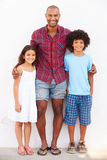 Father And Children Standing Outdoors Against White Wall� Royalty Free Stock Photos