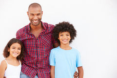 Father And Children Standing Outdoors Against White Wall� Royalty Free Stock Photo