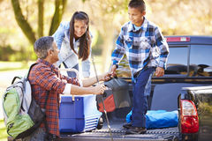 Father And Children Unpacking Truck On Camping Holiday. Smiling At Each Other stock photo