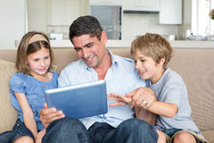 Father and children using digital tablet Royalty Free Stock Images
