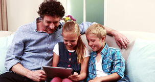 Father and children using tablet. On the sofa stock video
