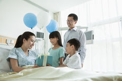 Father and children visiting their mother in the hospital, giving present and balloons stock image