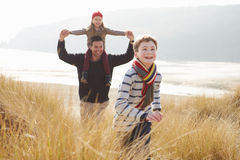 Father And Children Walking Through Dunes On Winter Beach stock photo
