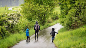 Father with children walking in rain Stock Image