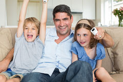 Father with children watching TV. Portrait of happy father with children watching TV at home Stock Photos
