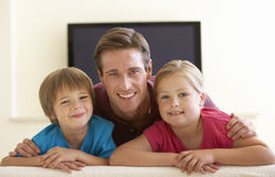 Father And Children Watching Widescreen TV At Home Stock Photo