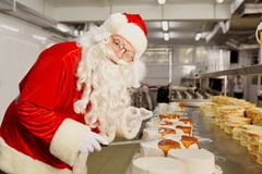Father Christmas bakes a cake at Christmas. Royalty Free Stock Images