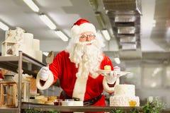 Father Christmas bakes a cake  at Christmas. Stock Photo
