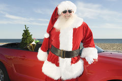 Father Christmas By Convertible With Christmas Tree. Father Christmas stands by red convertible with Christmas tree stock images