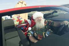 Father Christmas In Convertible With Surfboard Stock Photos