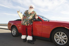 Father Christmas By Convertible With Surfboard. Father Christmas stands by red convertible with surfboard stock image