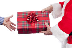 Father christmas handing over a tartan wrapped present Stock Photo