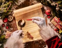 Father Christmas heating sealing wax on a candle flame above an old vintage scroll surrounded by Xmas decorations and gifts in an stock image